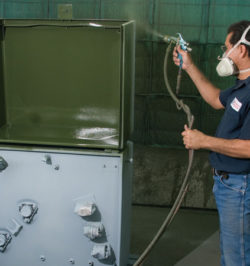 man with blue shirt and respirator spray painting equipment in green