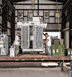 Three workers unloading truck with polemounts, substations and regulators